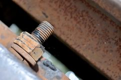 Den stora rostiga metallmuttern som låsas med rost, och korrosion kasta i sig, den industriella bulten och muttern royaltyfria foton