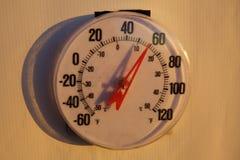 Den stora runda Weatherworn plast- termometern med den stora röda visaren säger It& x27; s nästan 60 grader utanför på soluppgång Royaltyfria Bilder
