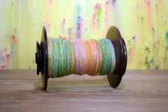 Den stora spolen för snurrhjulet som fylldes med våren färgade handen, rotera garn Royaltyfria Foton