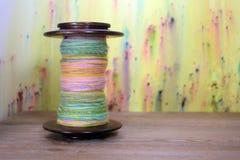 Den stora spolen för snurrhjulet som fylldes med våren färgade handen, rotera garn Arkivbild