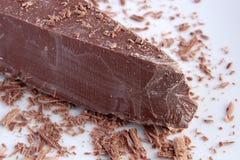 Den stora stora biten av mjölkar choklad och shavings arkivbilder