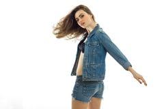 Den stora unga brunetten med härligt framkallande hår i jeans passar och att hålla hennes hand i framsidan och blickar på Royaltyfri Fotografi