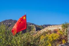 Den stora väggen av Kina på bakgrunden och det kinesiska BANRET för röd flagga, LÅNGT FORMAT fotografering för bildbyråer