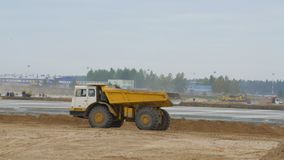 Den stora villebråddumper rider och att köra på konstruktionsplats Hårdna av flygplatslandningsbanavägar, huvudväg Konstruktion lager videofilmer