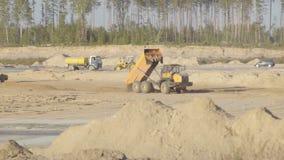 Den stora villebråddumper rider, person som ger dricks lastar av sand på konstruktionsplats Hårdna av flygplatslandningsbanavägar arkivfilmer