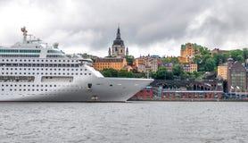 Den stora vita kryssningeyeliner är på pir mot stadslinjen, Stockholm, Sverige royaltyfri bild