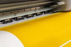 Den stora yrkesmässiga skrivaren som bearbetar ett glansigt ark för stor skala av gulingpapper, rullar för färgprovtagning fotografering för bildbyråer