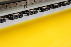 Den stora yrkesmässiga skrivaren som bearbetar ett glansigt ark för stor skala av gulingpapper, rullar för färgprovtagning royaltyfri fotografi