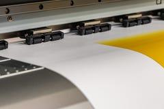 Den stora yrkesmässiga skrivaren som bearbetar ett glansigt ark för stor skala av gulingpapper, rullar för färgprovtagning royaltyfria bilder