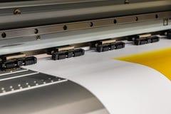 Den stora yrkesmässiga skrivaren som bearbetar ett glansigt ark för stor skala av gulingpapper, rullar för färgprovtagning arkivbilder