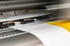 Den stora yrkesmässiga skrivaren som bearbetar ett glansigt ark för stor skala av gulingpapper, rullar för färgprovtagning royaltyfria foton