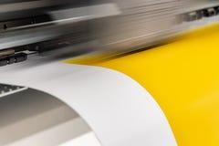 Den stora yrkesmässiga skrivaren som bearbetar ett glansigt ark för stor skala av gulingpapper, rullar för färgprovtagning royaltyfri foto