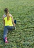Den sträckta löparekvinnan tvinnar i stadion som utomhus övar wearable teknologi för konditionbogserare Arkivfoto