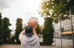 Den Streetball spelaren skjuter korgen Arkivbilder