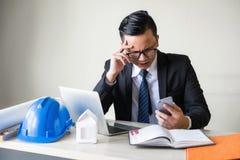 Den stressade affärsmannen läste dåliga nyheter vid smartphonen Royaltyfri Fotografi