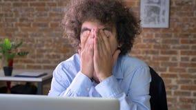 Den stressade affärsmannen med lockigt hår har problem med affären som sitter på tabellen med bärbara datorn i modernt kontor stock video