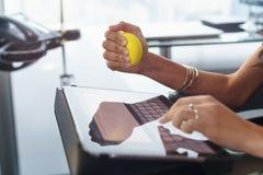 Den stressade kontorsarbetaren med anti-spänningsbollen skriver emailen Arkivfoton
