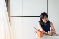 Den stressade kvinnan som använder minnestavlan som klarar av skuld, husräkningar med skatter och bankkontot balanserar royaltyfri fotografi