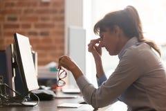 Den Stressed överansträngde mitt åldrades affärskvinnakontorsarbetaren som av tar exponeringsglas arkivfoton