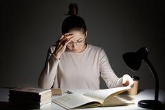Den stressiga skolflickan gör hem- assigment, skrivar om information från boken i anteckningsbok, håller handen på pannan, känner royaltyfri fotografi