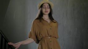 Den Stylishly klädda unga härliga flickan i elegant hatt går ner trappahandväskan i hand, begreppslivsstilmode och skönhet stock video