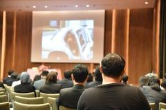 Den suddiga bilden av utbildningsfolk och affärsfolk som sitter i konferensrum för yrkeseminarium och högtalaren, är närvarande Royaltyfri Fotografi