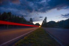 Den suddiga bilen tänder, det långa exponeringsfotoet av trafik Fotografering för Bildbyråer