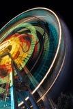 Den suddiga delen av en pariserhjul på natten med att ändra färgar Rida snurret som skapar ljusa strimmor på natten Royaltyfria Bilder