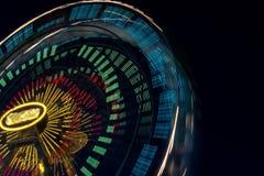 Den suddiga delen av en pariserhjul på natten med att ändra färgar Rida snurret som skapar ljusa strimmor på natten Arkivbilder