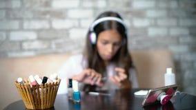 Den suddiga flickan i hörlurar och hemkläder som direktanslutet pratar på bitande telefondanandemanikyr, spikar arkivfilmer