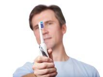 Den suddiga mannen ser isolerad vit för den elektriska tandborsten Arkivbild
