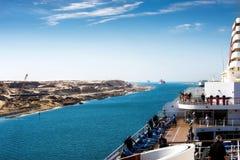 Den Suez kanalen - en skeppeskortfartyg med ett kryssningskepp passerar det nytt Arkivfoto