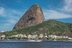Den Sugarloaf berg-, Urca grannskapen och Botafogo skäller med powerboaten i Rio de Janeiro Royaltyfri Foto