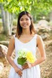 Den sunda asiatiska kvinnan i det vita klänninginnehavet blommar, och frukter på gräsplan parkerar Royaltyfria Foton