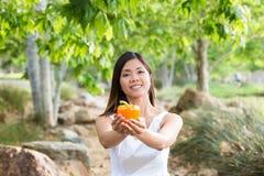 Den sunda asiatiska kvinnan i det vita klänninginnehavet blommar, och frukter på gräsplan parkerar Arkivbild