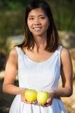 Den sunda asiatiska kvinnan i det vita klänninginnehavet blommar, och frukter på gräsplan parkerar Royaltyfria Bilder