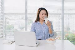 Den sunda asiatiska kvinnan som dricker ett exponeringsglas av, mjölkar på skrivbordet i regeringsställning arkivfoton