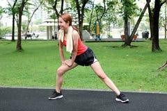 Den sunda asiatiska kvinnan som sträcker henne ben för inkört, parkerar Kondition- och övningsbegrepp arkivbild
