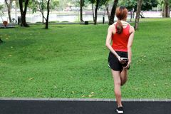 Den sunda asiatiska kvinnan som str?cker henne ben f?r ink?rt, parkerar Kondition- och ?vningsbegrepp arkivbild