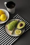 Den sunda avokadofrukosten skivade avokadot på rostat brödbröd med kryddor, citroner Kupa av kaffe Banta mat Morgonmat royaltyfri fotografi