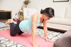 Den sunda förväntansfulla modern gör knäet Push-UPS på matt yoga Arkivbilder