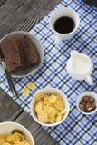 Den sunda frukostcornflakens, mjölkar, koppen av svart kaffe och skivachokladkakan arkivfoto