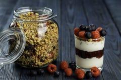 Den sunda frukosten av yoghurten med mysli, granolahallondriftstopp och nya frukter hallon och blåbär royaltyfria bilder