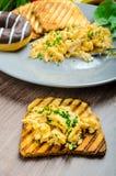 Den sunda frukosten förvanskade ägg med gräslöken, paninirostat bröd Royaltyfria Foton