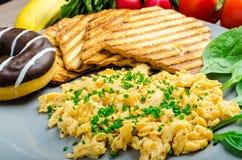 Den sunda frukosten förvanskade ägg med gräslöken, paninirostat bröd Arkivfoton