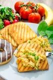 Den sunda frukosten förvanskade ägg med gräslöken, paninirostat bröd Arkivfoto