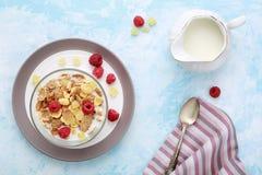 Den sunda frukosten flagar med hallon & mjölkar på blåtttabellen Arkivbilder