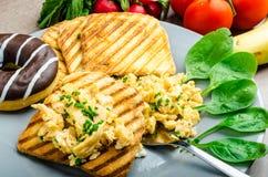 Den sunda frukosten förvanskade ägg med gräslöken, paninirostat bröd Arkivbild