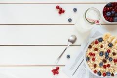 Den sunda frukosten med bär och mjölkar på den vita trätabellen med kopieringsutrymme, bästa sikt Arkivbilder