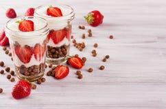 Den sunda frukosten med choklad klumpa ihop sig havreflingor, skivad jordgubbe på det vita wood brädet Dekorativ gräns med kopier Arkivbild